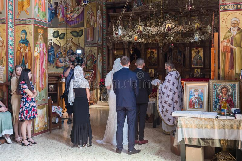 A priest reads a prayer at the wedding ceremony held in the Orthodox tradition in Greek Orthodox monastery of the twelve apostles royalty free stock photo