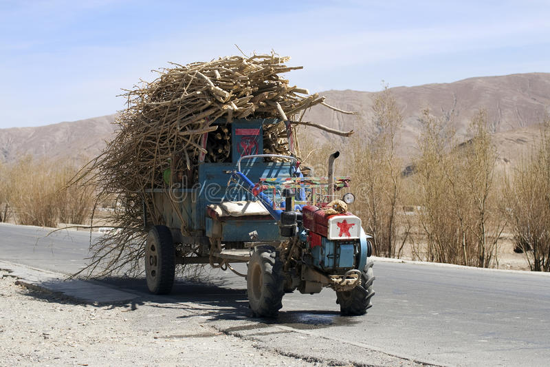 Tibet. Small tractor full with cut wood parked on road, Tibet stock photos