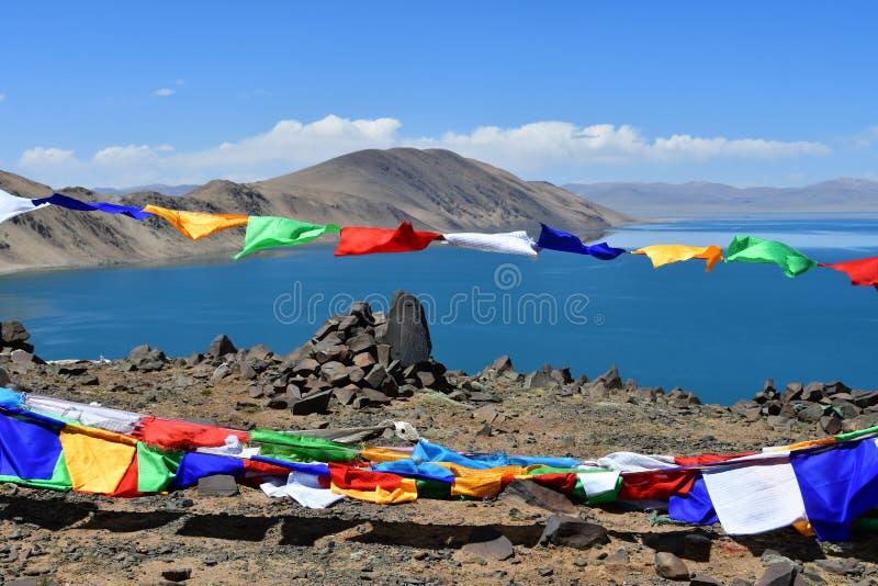 Tibet buddistiska flaggor med mantras framme av den heliga sjöBum Co sjön i solig dag för sommar arkivfoto
