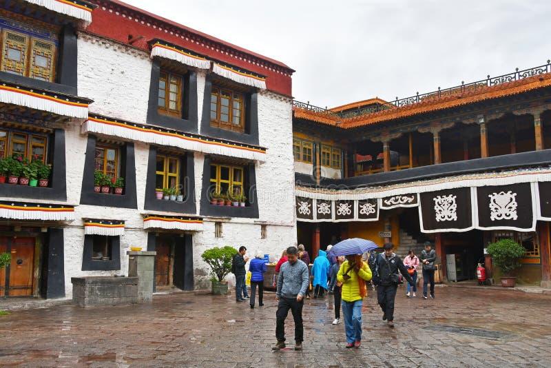 Tibet, Lhasa, China, 03 Juni, 2018 De mensen zijn in de binnenplaats van de oude Boeddhistische tempel Jokang in bewolkt weer stock foto