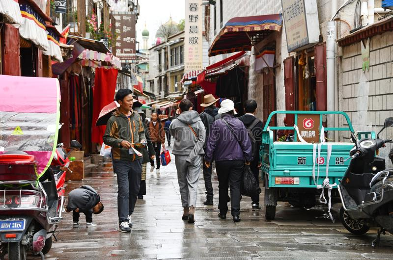 Tibet, Lhasa, China, 03 Juni, 2018 De mensen zijn op de straat in het historische centrum van Lhasa in regenachtig weer Tibet, Ch stock foto