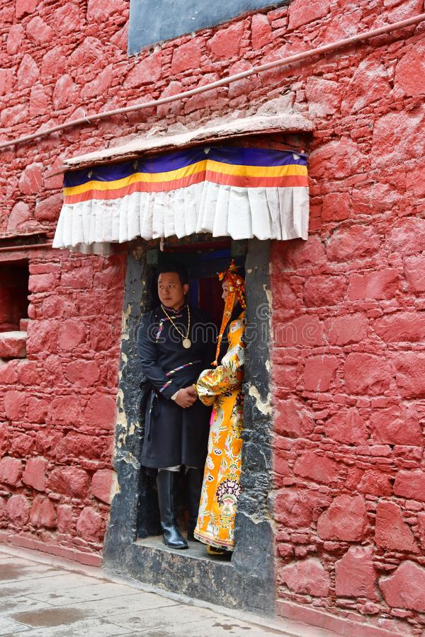 Tibet, Lhasa, China, 03 Juni, 2018 Jong paar van mensen in nationale kostuums die zich in de deuropening van oud klooster bevinde stock foto