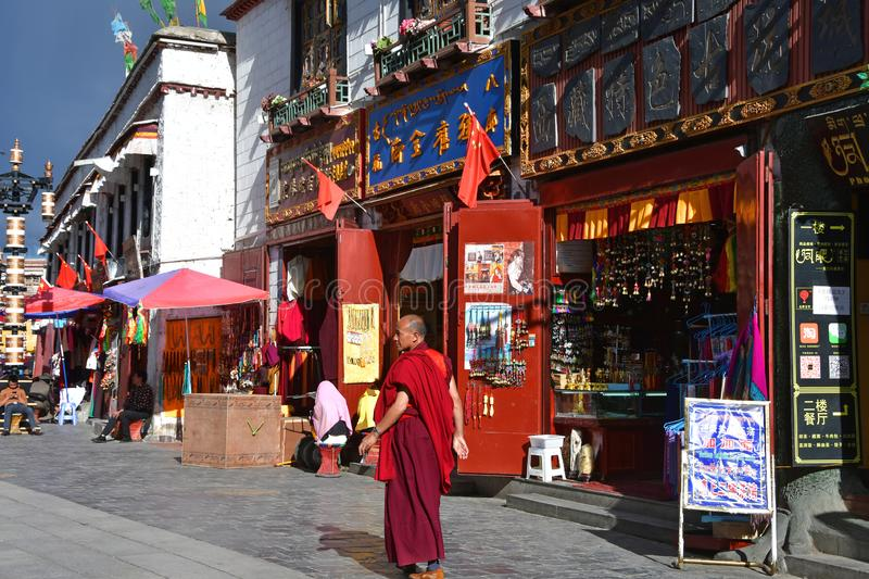 Tibet, Lhasa, China, June, 02, 2018.   Monk walking along the ancient Barkhor street on a summer day in cloudy weather royalty free stock photos