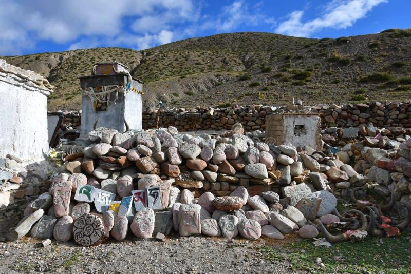 tibet Whate-stupa und buddhistische Gebetssteine mit Beschw?rungsformeln und Ritualzeichnungen auf der Spur von der Stadt von Dor lizenzfreie stockfotografie