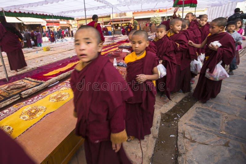 Tibetaanse Boeddhistische monniken dichtbij stupa Boudhanath tijdens feestelijke Puja stock afbeelding