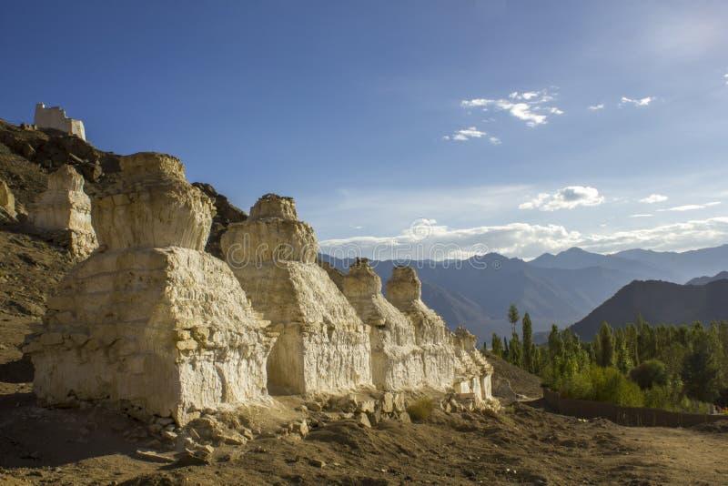 Tibetaanse Boeddhistische witte tempels van stupa op een steenachtige helling tegen de achtergrond van een bergvallei onder een b royalty-vrije stock foto