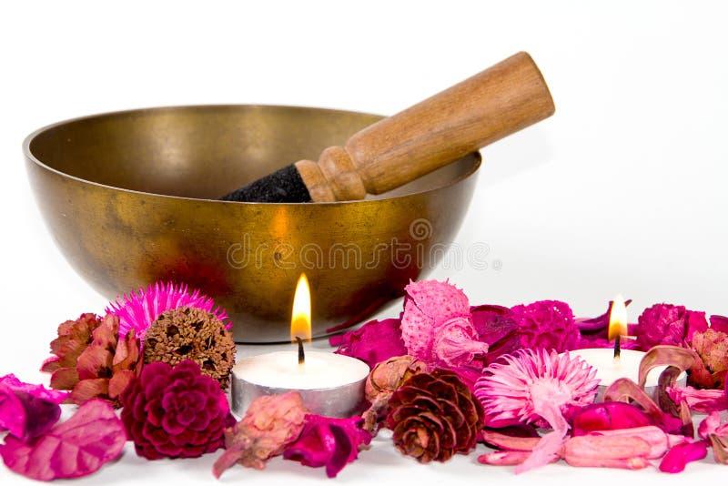 Tibetaanse kom, bloemen en kaarsen. stock afbeeldingen