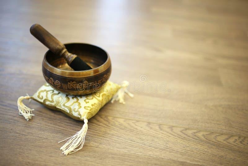 Tibetaanse Singing Bowl over Zijdergele kussen en de achtergrond van hout stock afbeelding