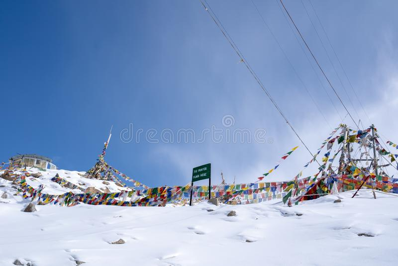Tibetan bönflagga på Khardung La i vinter Khardung La är ett bergpasserande i den Ladakh regionen av den indiska staten av Jammu  arkivbild