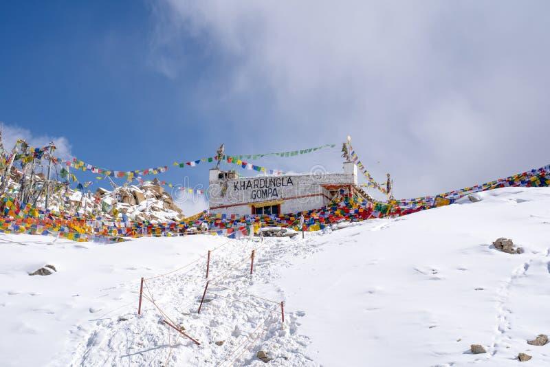 Tibetan bönflagga på Khardung La i vinter Khardung La är ett bergpasserande i den Ladakh regionen av den indiska staten av Jammu  royaltyfria bilder