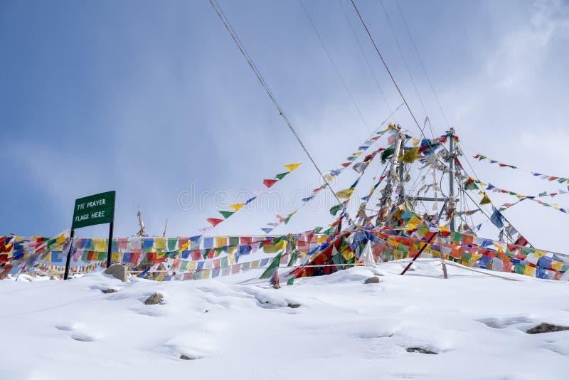 Tibetan b?nflagga p? Khardung La i vinter Khardung La ?r ett bergpasserande i den Ladakh regionen av den indiska staten av Jammu  royaltyfri foto