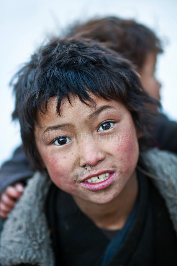 Tibetan boys, Nepal. LHO, GORKHA, NEPAL - NOVEMBER 28: Tibetan boy are carrying him baby brother poses for a photo on the road to Lho village on November 28 royalty free stock photography