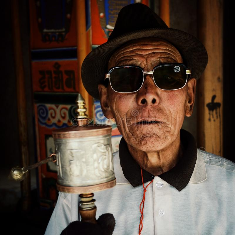 tibetan buddhist pilgrim man during his pilgrimage circle around the temple with a hand held mobile prayer wheel front of a big fi royalty free stock image