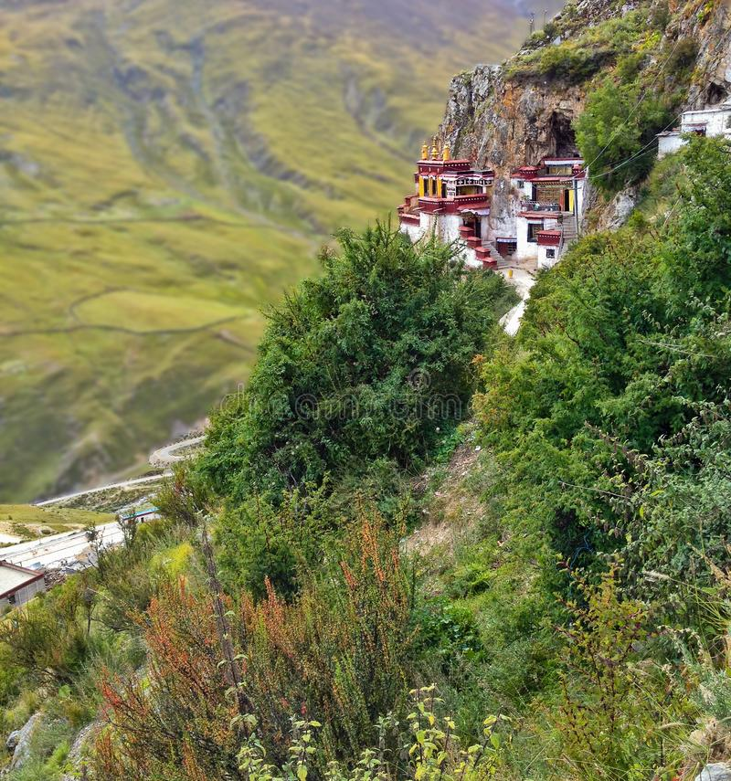 Tibetan Drak Yerpa Buddhist monastery on the cliff in Mountains of Tibet. The Holiest caves for meditation and place for pilgrim. Age, hermitage or retreat near royalty free stock photos