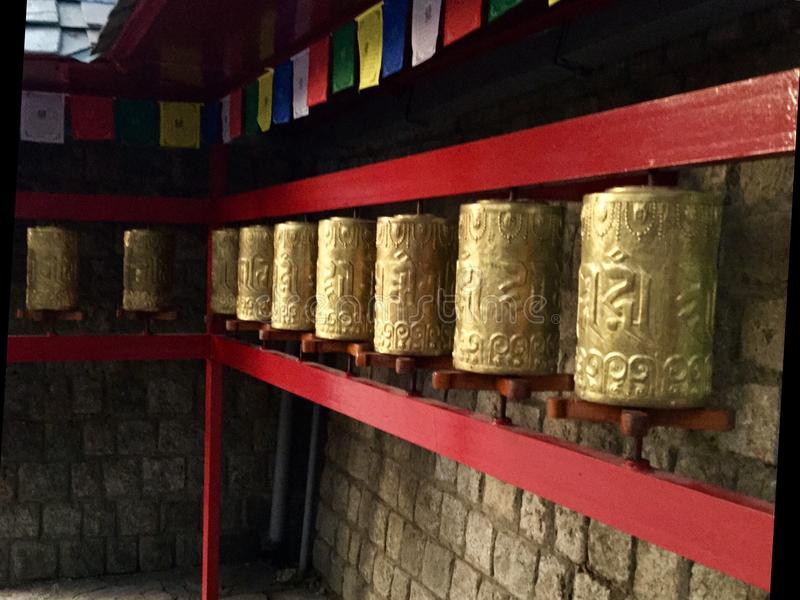 Tibetan Golden Prayer Wheels, Dharamsala, India. A prayer wheel is a cylindrical wheel on a spindle made from metal, wood, stone, leather or coarse cotton royalty free stock photos