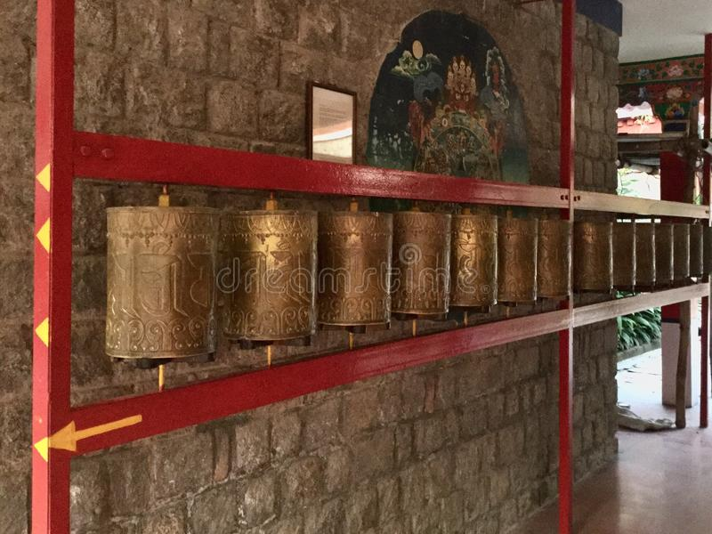 Tibetan Golden Prayer Wheels in , Dharamsala, India. A prayer wheel is a cylindrical wheel on a spindle made from metal, wood, stone, leather or coarse cotton royalty free stock image