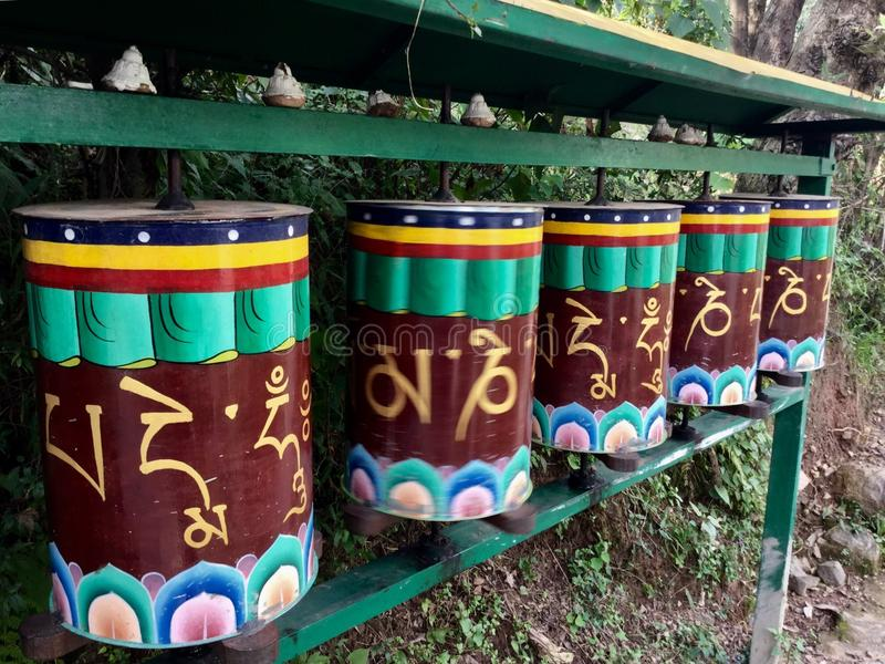 Tibetan Golden Prayer Wheels , the Kora Walk , McLeodgange, Dharamsala, India. A prayer wheel is a cylindrical wheel on a spindle made from metal, wood, stone stock images