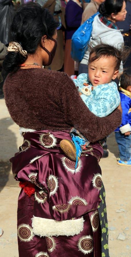 Tibetan kvinna som bär hennes barn royaltyfri bild