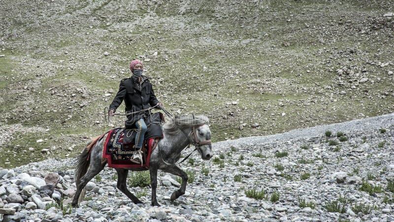 Tibetan man riding a horse stock images