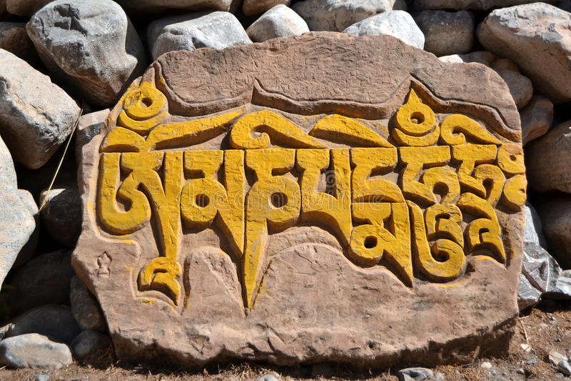 Tibetan mani stone. Tibetan text engraved on stone Mani stones are stones that are carved with the famous Sanskrit mantra o? ma?i padme hū?, as a form of stock photography