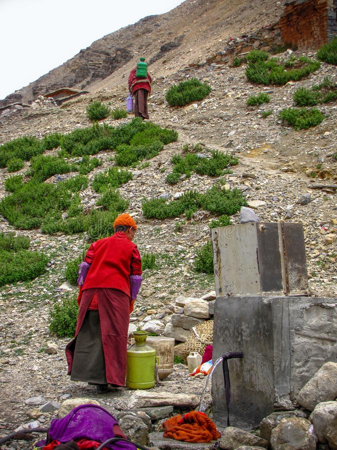 Tibetan men getting water at a tap, Rongbuk, Tibet, China. Ordinary tibetan people working hard washing clothes and filling cans at a water tap in Rongbuk near stock images