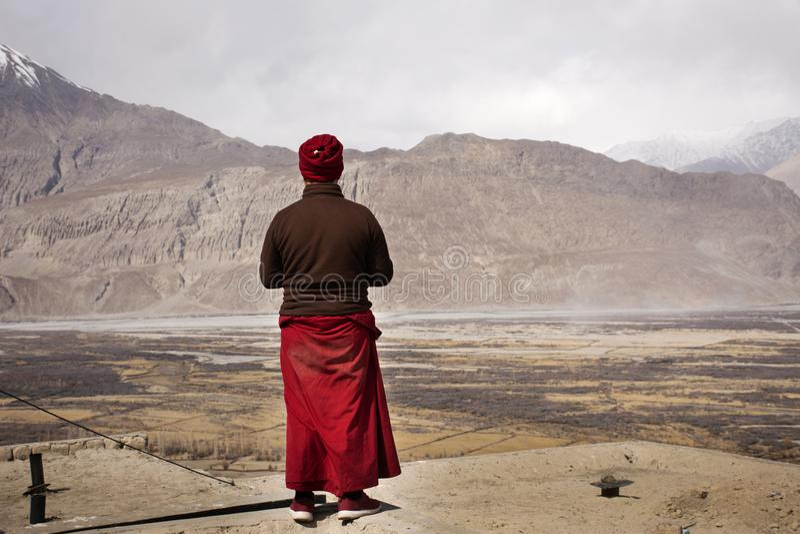 Tibetan monk pilgrim people stand on cliff Diskit Monastery Galdan Tashi Chuling Gompa looking view in Hunder or Hundar village stock photo