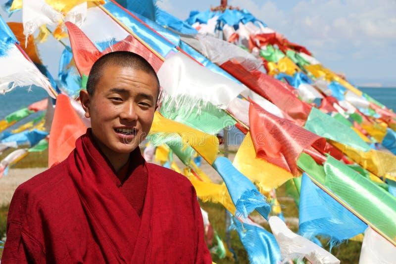 Tibetan monk with prayer flags stock image