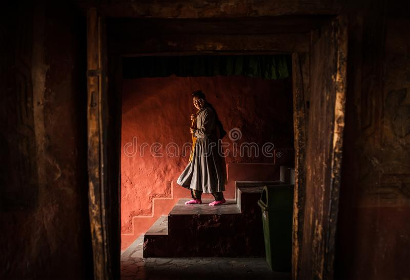 Tibetan monk woman goes down the stairs in Thiksey Monastery royalty free stock images