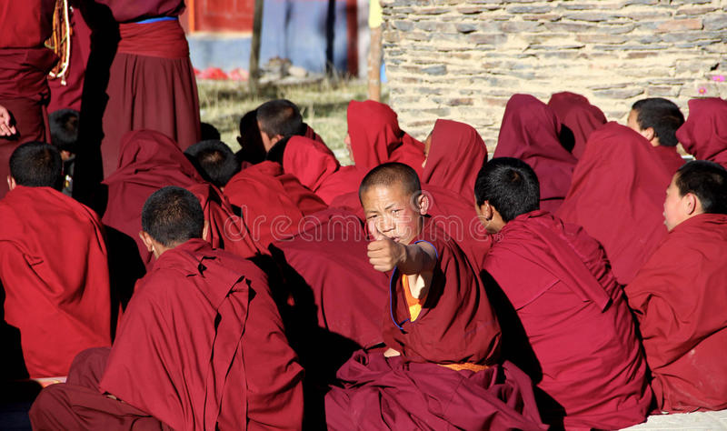 Tibetan monks sit together on a square. royalty free stock image