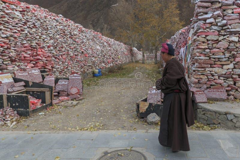 Tibetan munk som framme går av den Mani stenväggen med den buddistiska mantraen Om Mani Padme Hum som inristas i tibetant i Yushu royaltyfri foto
