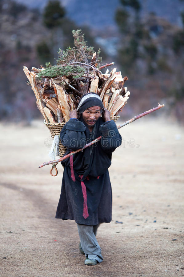 Tibetan peasant in national clothes with basket royalty free stock photo