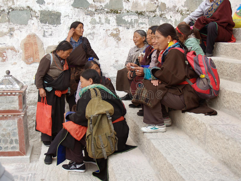 Tibetan people in Lhasa. LHASA, TIBET - SEPTEMBER 8, 2009: Tibetan people sitting on the stairs to the Potala Palace, talking, commenting and at leisure stock photography