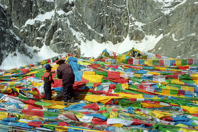 Tibetan pilgrims father and son are hanging the prayer flags Lungta on Drolma La Pass. royalty free stock photos