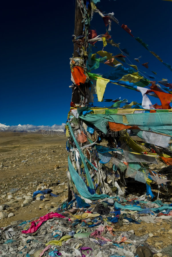 Tibetan prayer flags. Colourful tibetan banners/flags used for prayers in a mountaineous region. Old, weathered and torn flags visible in the foreground royalty free stock photos