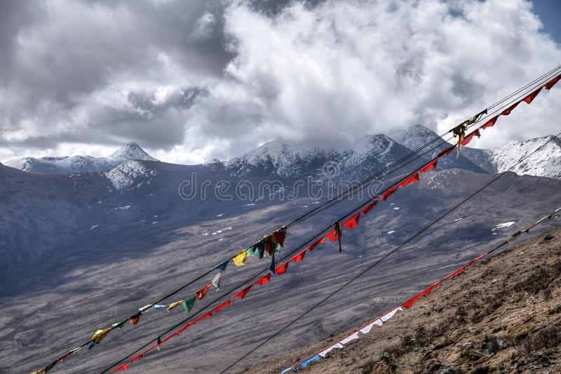 Tibetan prayer flags flutter in the wind. Himalayas in the background. stock photo