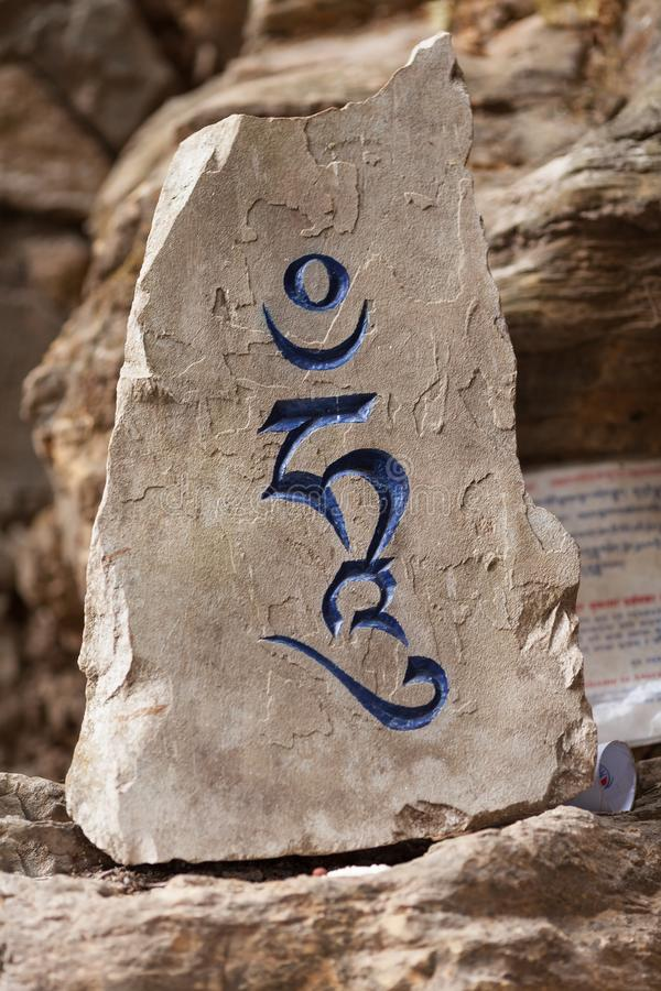 The Tibetan religious syllable `hung`. The Tibetan syllable `hung` which representing the Dkharmakaya carved on a stone and covered with blue paint stock photos