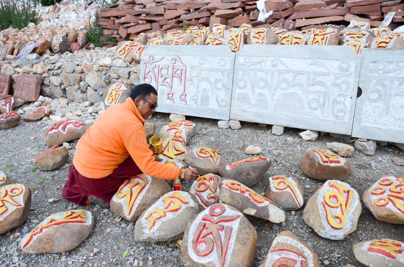 Tibetan rock painting artist stock photo