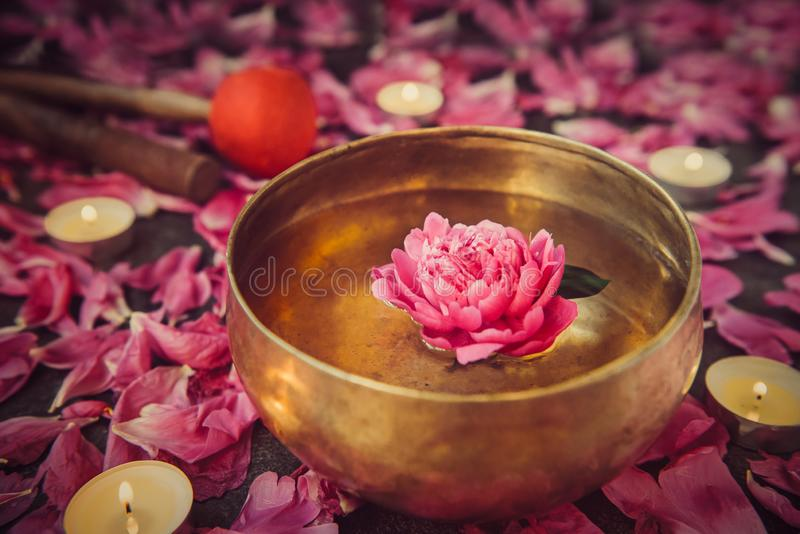 Tibetan singing bowl with floating inside in water pink peony flower. Burning candles, special sticks and petals on the black ston royalty free stock photos