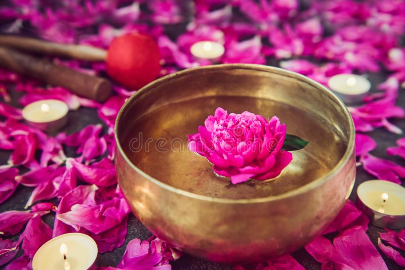 Tibetan singing bowl with floating inside in water purple peony flower. Burning candles, special sticks and petals on the black. Stone background. Meditation stock photography