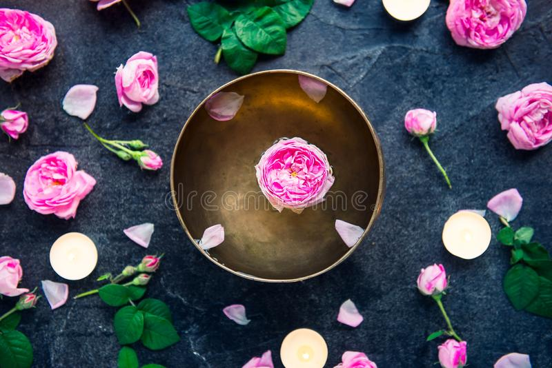 Tibetan singing bowl with floating rose inside. Burning candles, tea rose flowers and petals on the black stone background. Medita stock photo