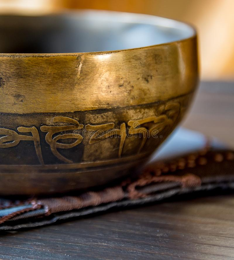 Tibetan singing bowl on top of a wooden table stock photography