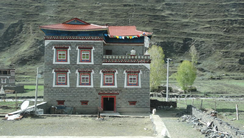 Tibetan style house in Xinduqiao, Sichuan. A typical Tibetan style house in a scenic rural area in Sichuan, China. The houses are usually squarish, with well royalty free stock image