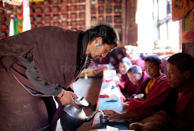 Tibetan tea ceremony, Nepal. LHO VILLAGE, NEPAL - NOVEMBER 28: Buddhist monks drinking tibetan tea during puja ceremony at monastery on november 28, 2009 in Lho royalty free stock image