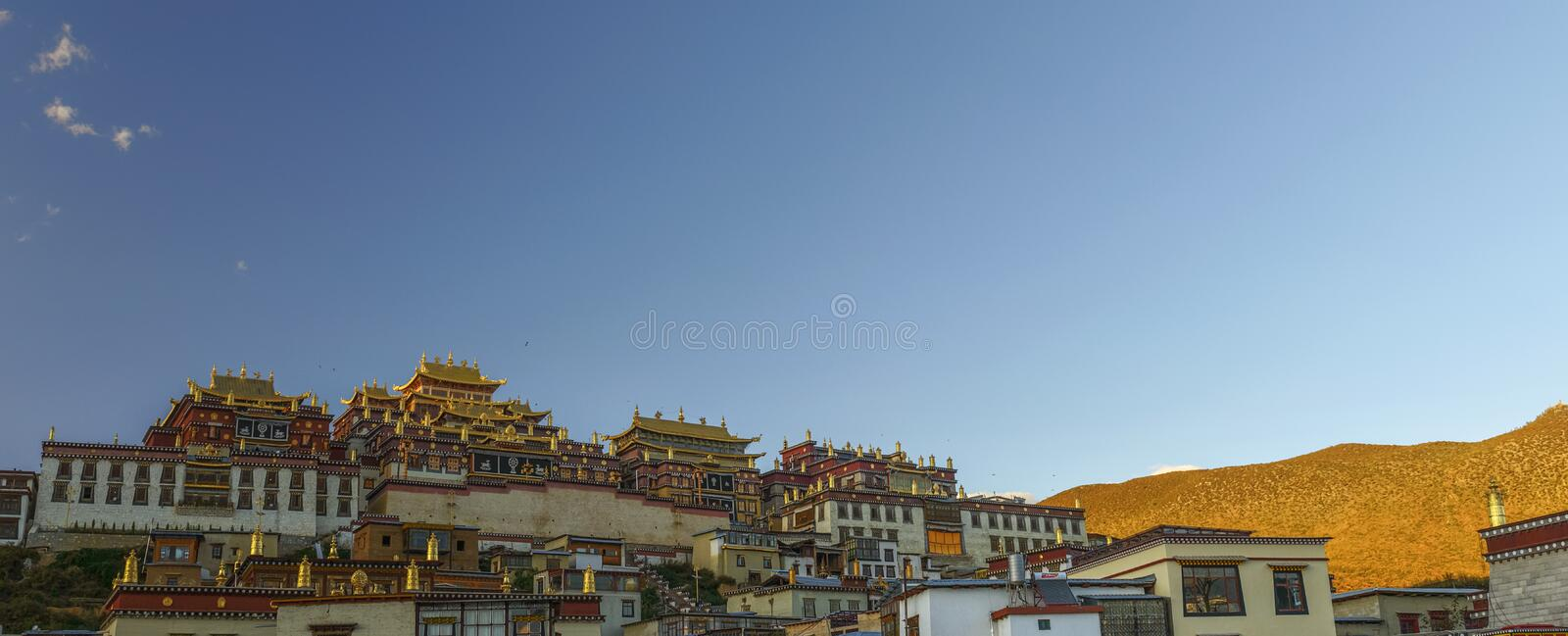 Tibetan temple at sunset. Tibetan temple landscape at songzhanlin temple, Shangri La, sunset time, with blue sky background royalty free stock photos