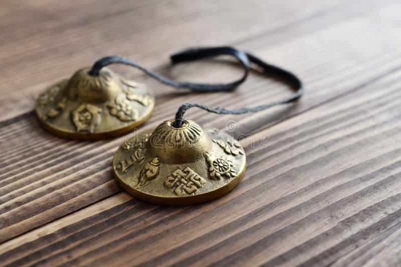 Tibetan Ting Sha Ceremonial Bells. On wooden background closeup royalty free stock photos