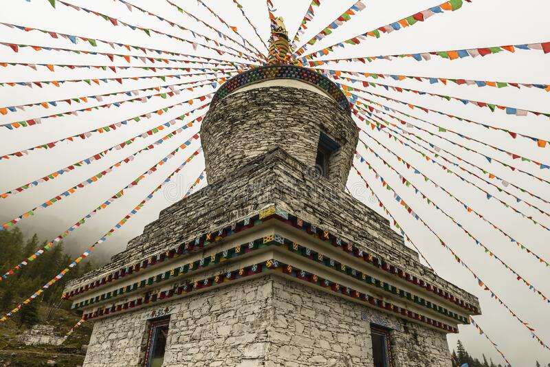 Tibetan white tower with Prayer Flags. In shuangqiao ditch, at siguniang Mount in windy day, from low viewpoint stock photo