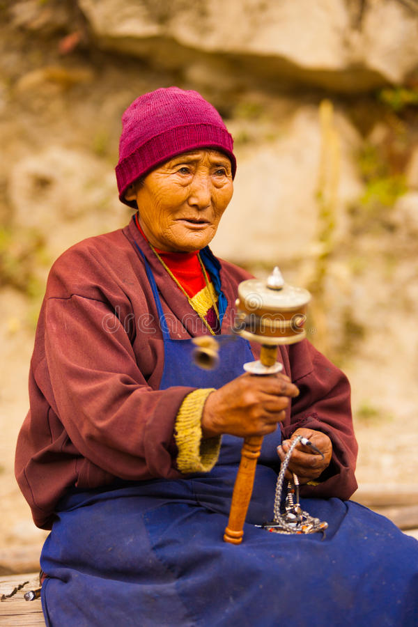 Tibetan Woman Pilgrim Praying Spinning Mani Wheel stock images