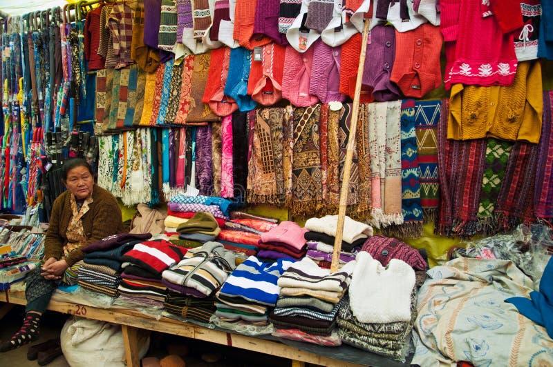 Tibetan woman selling woolen garments. DARJEELING, INDIA - APRIL 14: Tibetan woman sells colorful hand woven woolen garments at Darjeeling Mall Chowrasta market royalty free stock photos