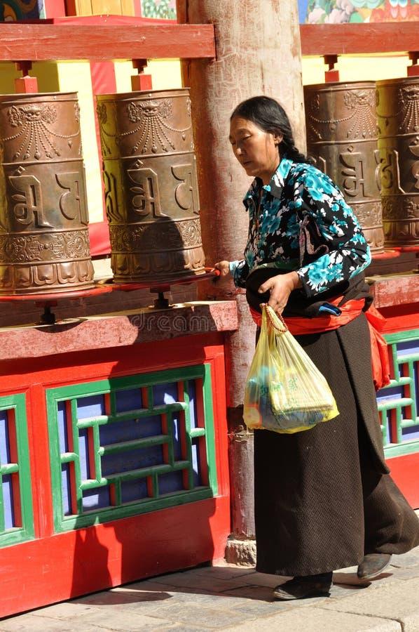 A Tibetan woman turning prayer wheels royalty free stock images