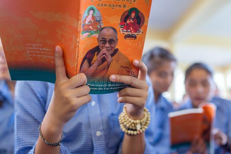Tibetana elever som lyssnar till hans helighet 14na Dalai Lama Tenzin Gyatso som ger undervisningar i hans uppehåll i Dharamsala, royaltyfri fotografi